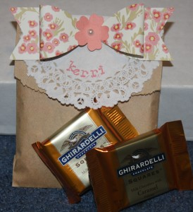 "This  brown bag with cute paper bow and doily says on the back - It is such a ""treat"" to have you here!"