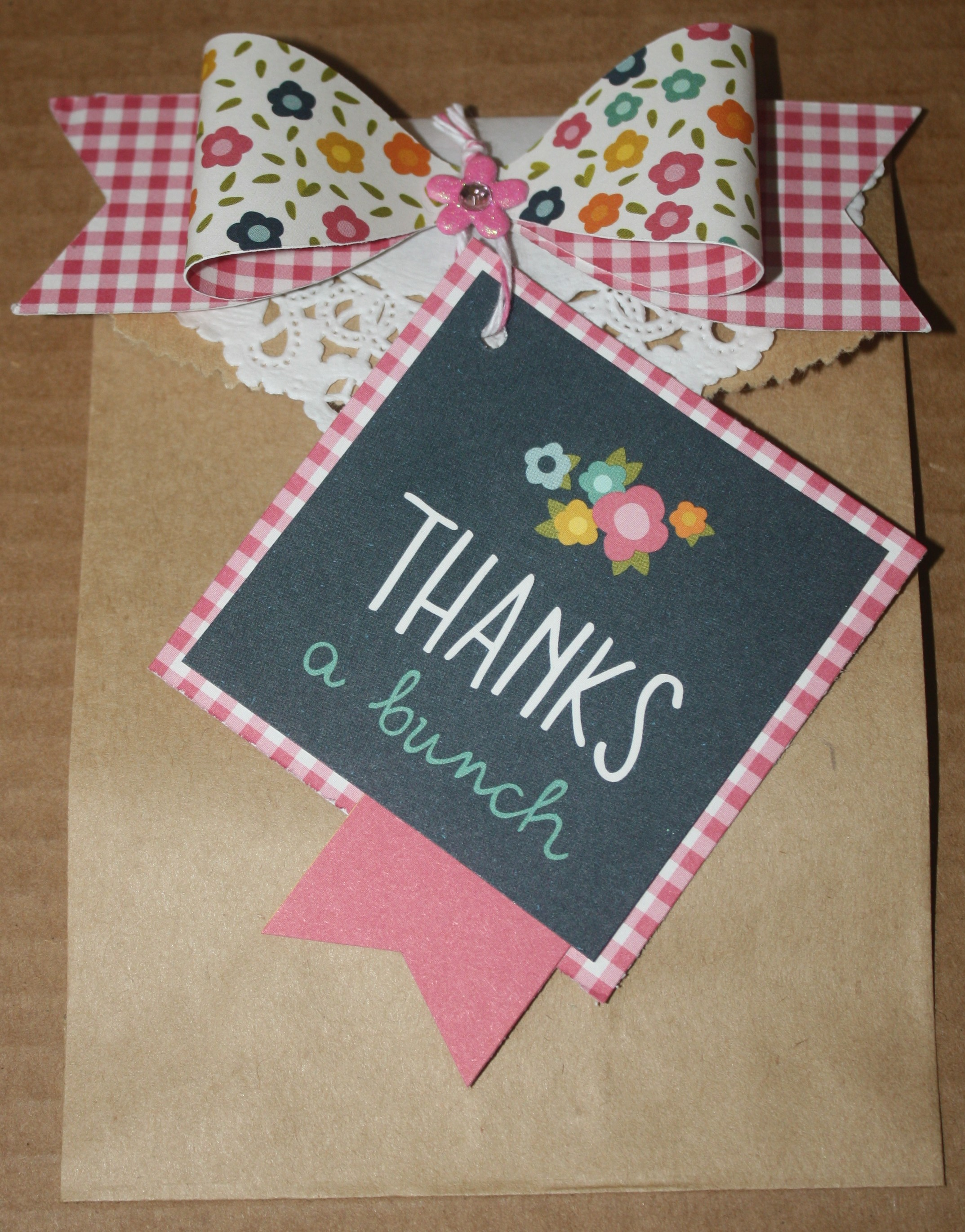 This simple flat kraft bag became a real beauty when I added a die cut bow, a Doodlebug brad, and a doily with the Thanks a bunch square.  The bag could have any kind of treat placed in it but I have tried it out and found that 2 flat square Ghirardelli chocolates fit side by side just perfectly. I layered the square on the same Sunny Side paper that the bow was diecut from.  I got the diecut and the doily from Pebbles in my Pocket!