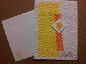 "Used a simple white card base - added some yellow pattern paper and a strip of orange washi tape - then used an embossing folder to add the swirls - on a 1"" square I stamped this lightbulb - in the corner stamped You Light Up My Life"